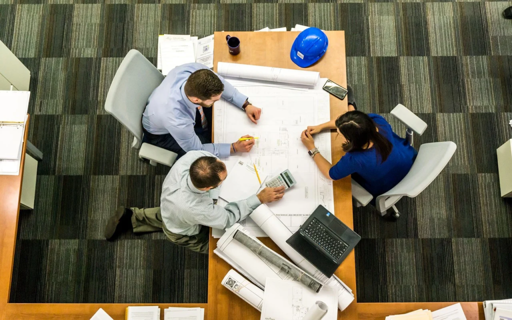 A top-down view of three people in a meeting, going over schematics.
