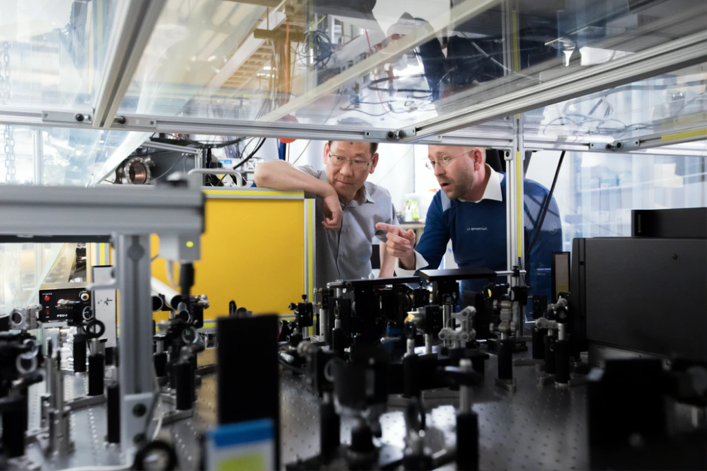 Two men looking at electrical components for a machine.